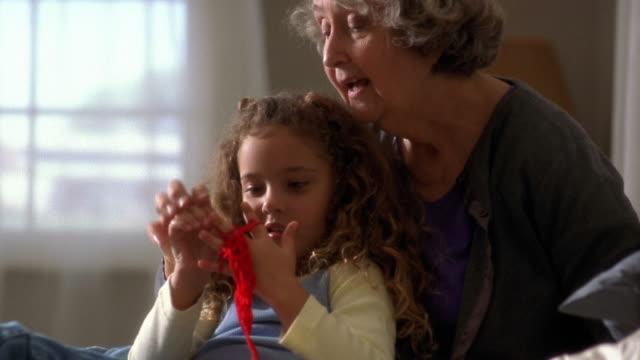 vidéos et rushes de medium shot tilt up senior woman and little girl playing with yarn - nurse