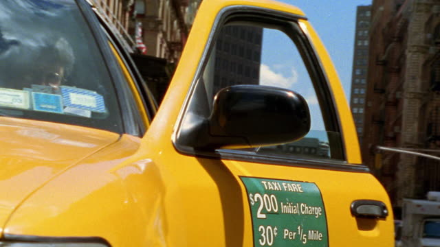 Medium shot tilt up taxi driver getting out of car and giving thumbs up / NYC