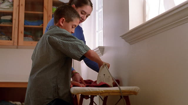 vídeos y material grabado en eventos de stock de medium shot tilt up teenage girl helping boy iron clothes on ironing board - tabla de planchar