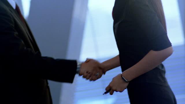 Medium shot tilt up tilt down businesswoman shaking hands with businessman