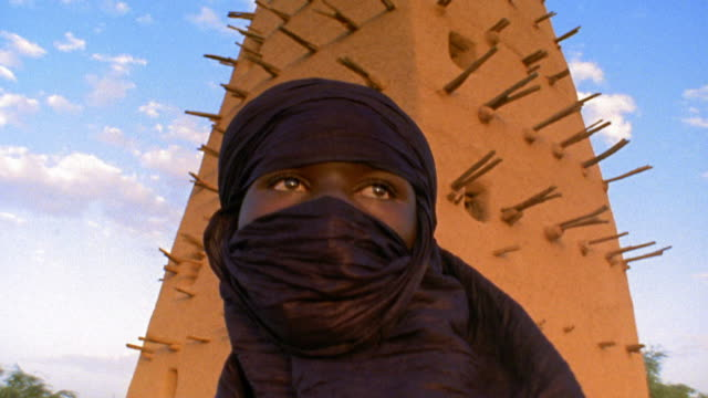 Medium shot tilt up Tuareg tribesman wearing shesh headdress standing in front of Agadez Mosque / Niger