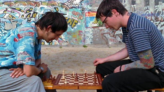 medium shot tilt up two men playing chess on beach / eastside beach, berlin - chess stock videos & royalty-free footage