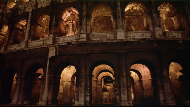 medium shot tilt up view of the colosseum illuminated at night / rome - bogen architektonisches detail stock-videos und b-roll-filmmaterial