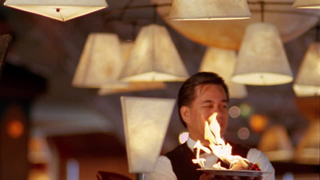 vídeos y material grabado en eventos de stock de medium shot tilt up waiter holding plate w/flaming dessert in restaurant w/white lampshades hanging from ceiling - hospitalidad a los clientes