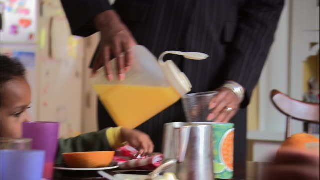 medium shot tilt up woman in suit pouring orange juice at breakfast table with son in foreground / passing glass to husband - berufstätige mutter stock-videos und b-roll-filmmaterial