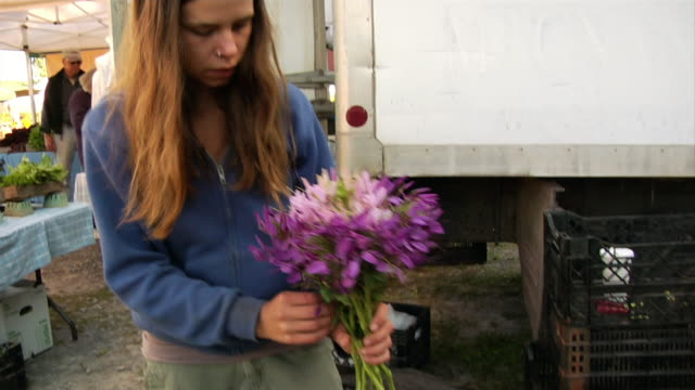 medium shot tilt up woman putting together bouquet of flowers at farmers' market - nose piercing stock videos & royalty-free footage
