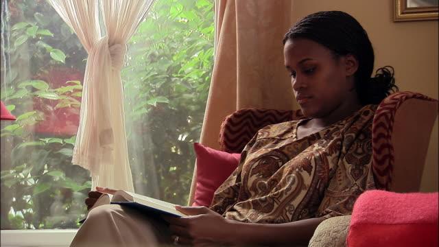 vidéos et rushes de medium shot tilt up woman sitting in chair by window and reading - prendre sur les genoux