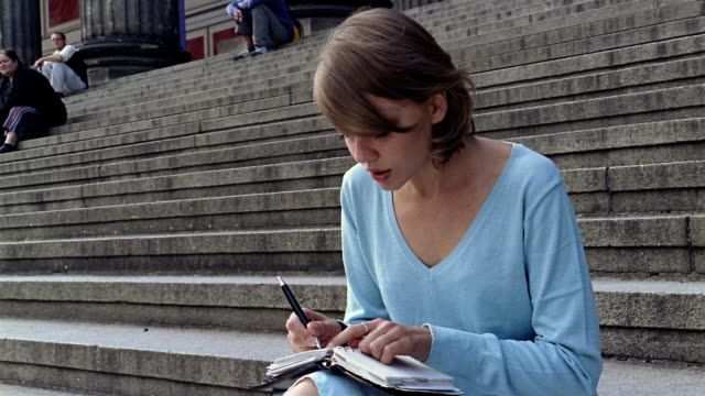 medium shot tilt up woman writing in diary on steps of the altes museum (old museum) / berlin - solo ragazze video stock e b–roll