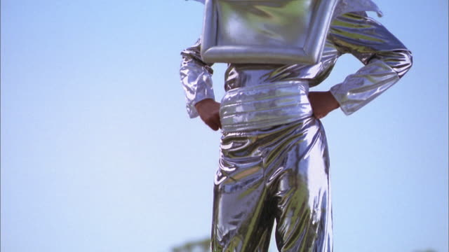 medium shot tilt up young girl posing outdoors in silver astronaut costume and helmet - verkleidung kleidung stock-videos und b-roll-filmmaterial