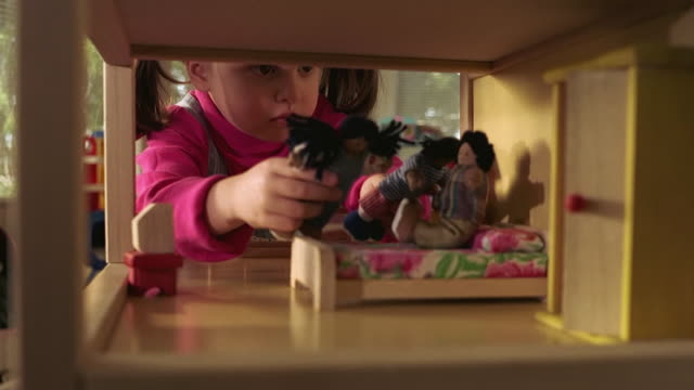 medium shot tilt up young hispanic girl putting dolls on miniature bunkbed in dollhouse - dollhouse stock videos & royalty-free footage