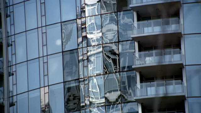 medium shot tilt up zoom out reflections in windows of steel and glass building in vancouver / british columbia, canada - kelly mason videos stock videos & royalty-free footage