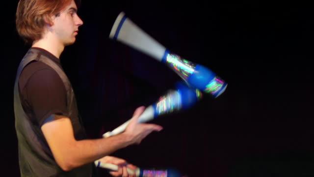 medium shot tilt-up pan man juggling clubs - juggling stock videos & royalty-free footage