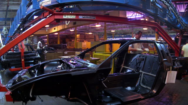 stockvideo's en b-roll-footage met medium shot time lapse automobile workers working on car bodies (pontiac fiero) on assembly line / detroit, michigan - autofabriek