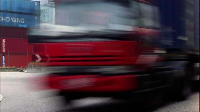 Medium shot time lapse cargo trucks and other traffic merging into one lane on highway / Hong Kong