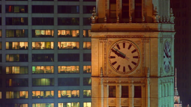 Medium shot time lapse clock hands moving on clock tower with lights turning on and off in building in background / Chicago, Illinois
