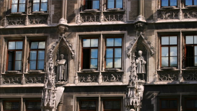 medium shot time lapse clouds reflected in the windows of the rathaus / munich - statue stock-videos und b-roll-filmmaterial