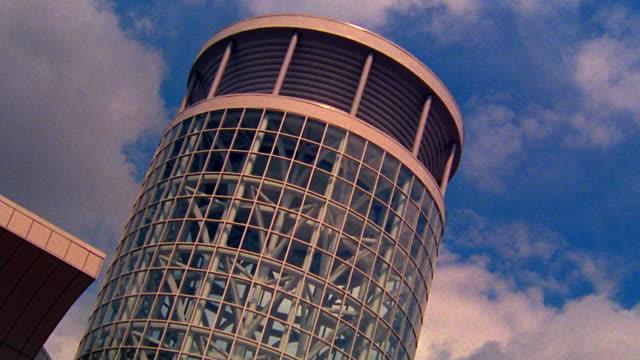 Medium shot time lapse clouds rolling behind circular glass building in Salt Lake City / Utah