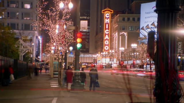medium shot time lapse crowds crossing street and traffic moving on downtown street at night / chicago - 2002 stock videos & royalty-free footage