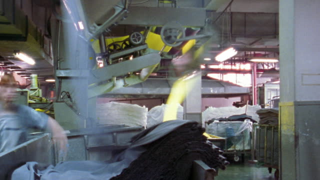 medium shot time lapse machine dropping sheets of fabric into a pile in textile factory / korea - textile mill stock videos & royalty-free footage