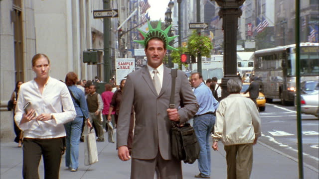vídeos de stock, filmes e b-roll de medium shot time lapse pedestrians walking as businessman stands w/foam statue of liberty crown - personas de negocios