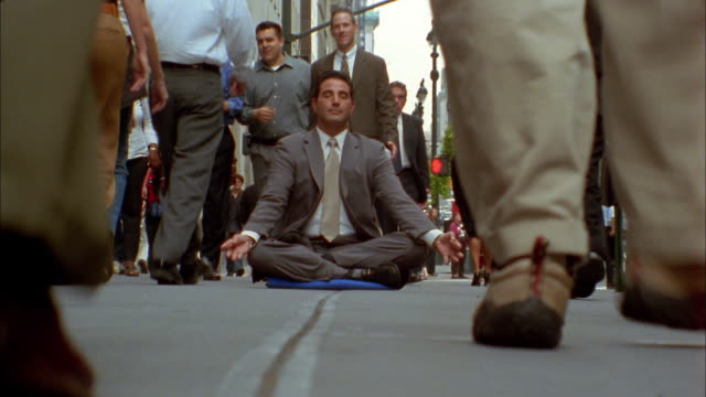 Medium shot time lapse pedestrians walking / businessman sitting in lotus position on sidewalk