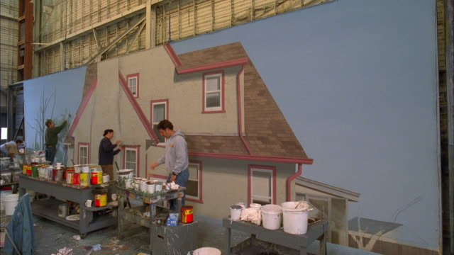 Medium shot time lapse scenic artists painting house backdrop on soundstage / Warner Brothers studios