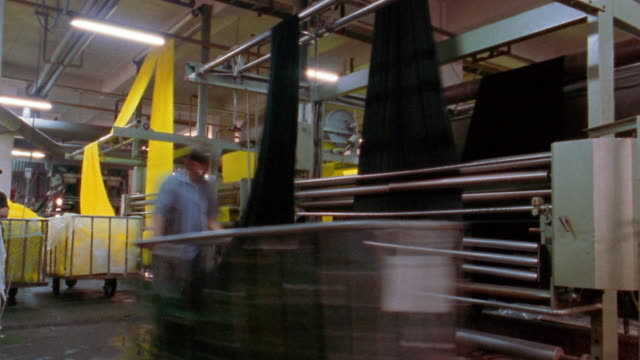 medium shot time lapse sheets of fabric passing through rollers into carts in textile factory - 2003 stock videos & royalty-free footage