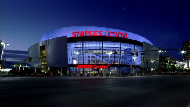 medium shot time lapse staples center at night w/traffic in foreground - staples center video stock e b–roll