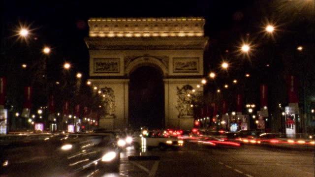vidéos et rushes de medium shot time lapse traffic in front of arc de triomphe at night / paris - arc élément architectural