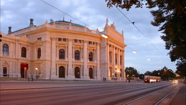 medium shot time lapse traffic outside burgtheater / vienna - tram stock-videos und b-roll-filmmaterial