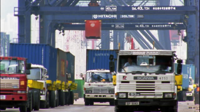 medium shot time lapse trucks being unloaded and loaded with large shipping containers / hong kong - haulage stock videos & royalty-free footage