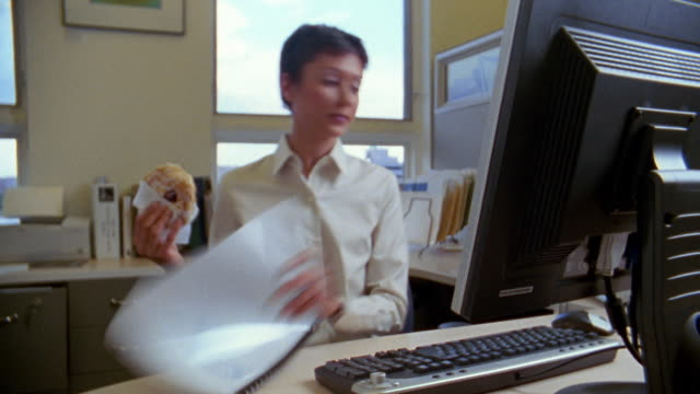 Medium shot time lapse woman with pastry in hand at desk answering phone and handling files / Albuquerque, NM