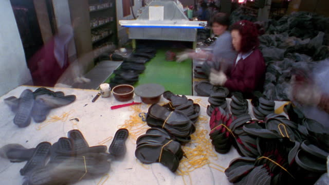 Medium shot time lapse women unwrapping bundles of shoe soles and placing them on conveyor belt in factory / Korea