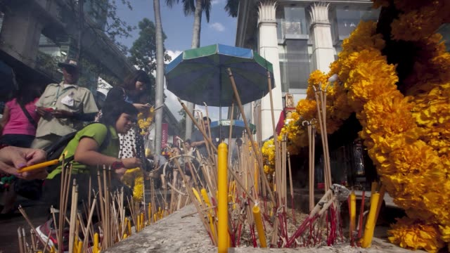 Medium shot timelapse pan right to left of worshippers praying with incense sticks at Erawan Shrine in the Pathum Wan district of Bangkok Thailand on...