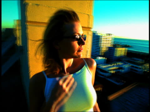 vídeos de stock, filmes e b-roll de medium shot to close up young woman watching sunset over ocean from rooftop / los angeles, california - imagem tonalizada