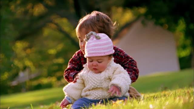 vidéos et rushes de medium shot toddler brother sitting behind baby sister outdoors - soeur