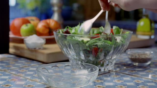 Medium shot tossing salad in glass bowl / serving salad in glass dish