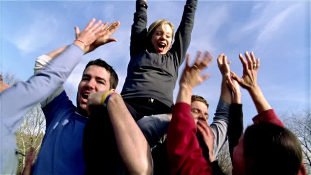 medium shot touch football teammates carrying woman on their shoulders in victory/ maine - touch football stock videos & royalty-free footage