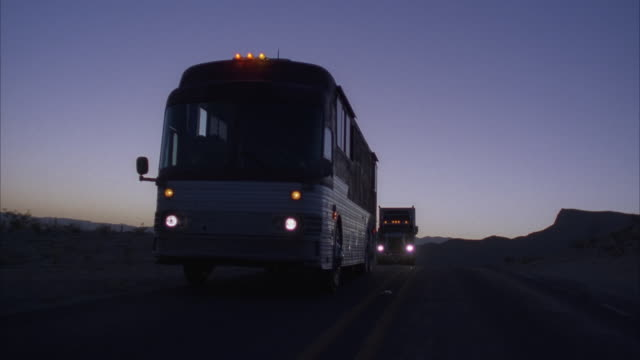 Medium Shot, Tour bus and truck driving on highway at dusk, USA