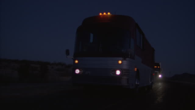 Medium Shot, Tour bus and truck driving on highway at night, USA