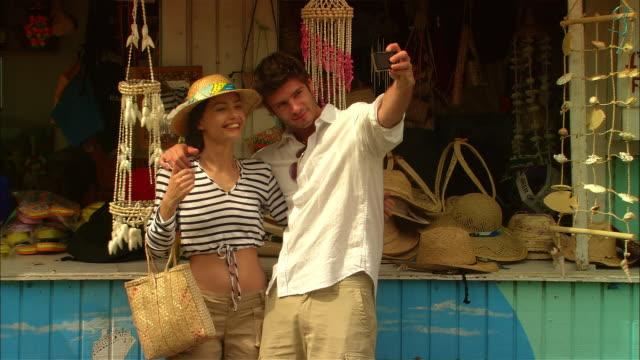 medium shot tourist couple shopping at roadside gift shop/ harbor island, bahamas - お土産点の映像素材/bロール