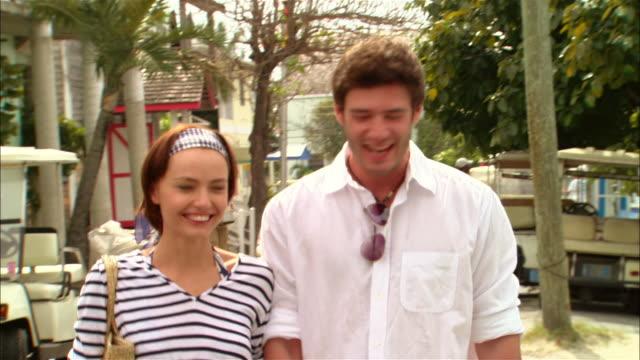vidéos et rushes de medium shot tourist couple shopping at roadside gift shop/ harbor island, bahamas - tourisme