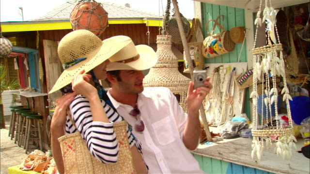 medium shot tourist couple shopping at roadside gift shop/ harbor island, bahamas - souvenir stock videos and b-roll footage