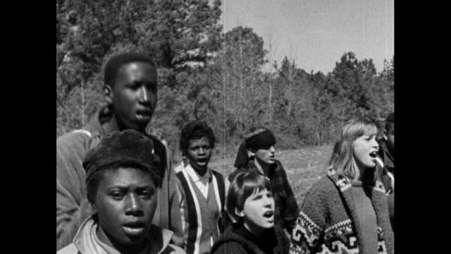 "medium shot tracking alongside a group of protest marchers marching along the highway from selma to montgomery, singing ""we shall overcome""; 22nd... - black civil rights stock videos & royalty-free footage"