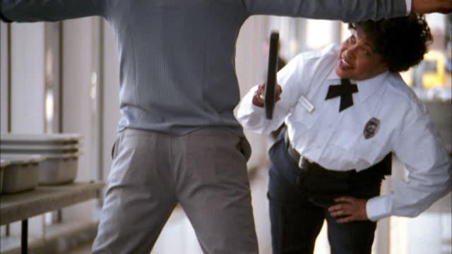 Medium shot tracking shot airport security worker scanning man w/metal detector and talking