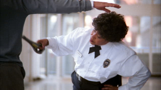 Medium shot tracking shot airport security worker scanning man's legs w/metal detector