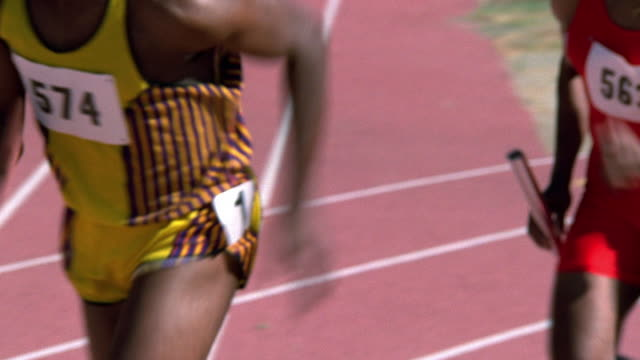 stockvideo's en b-roll-footage met medium shot tracking shot black male runner passing baton to teammate during relay race - elasthaan