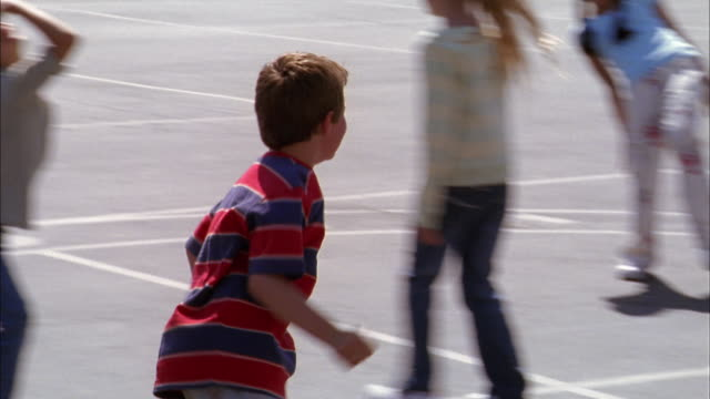 Medium shot tracking shot boy running and tagging other children in freeze tag game on playground