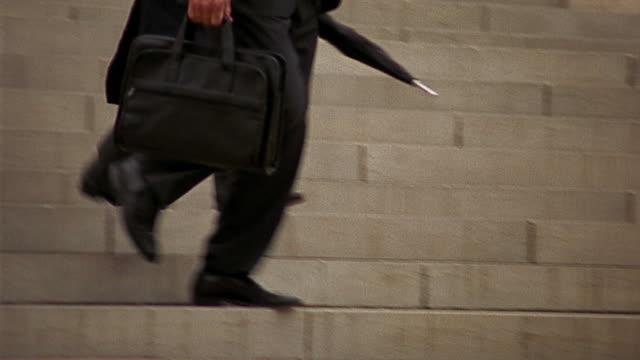 Medium shot tracking shot businessmen's legs and feet walking down steps