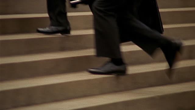Medium shot tracking shot businessmen's legs+ feet walking up steps